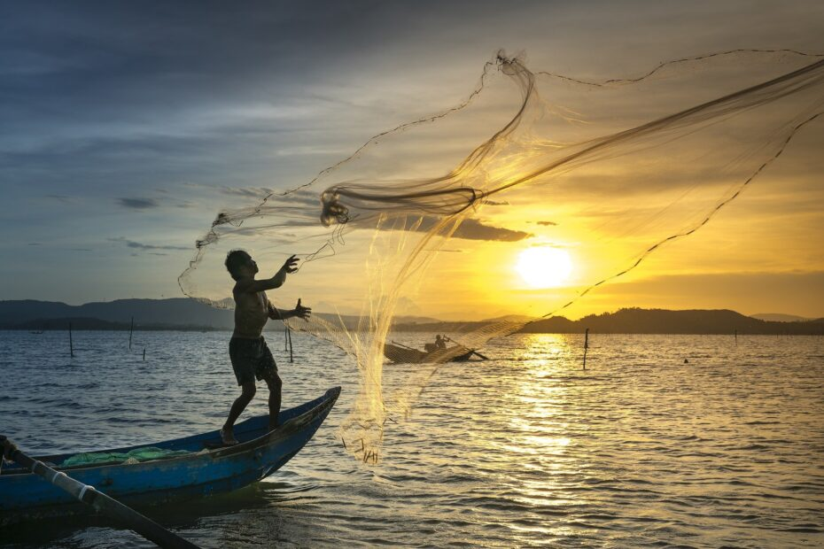 fisherman throwing a net off a small boat