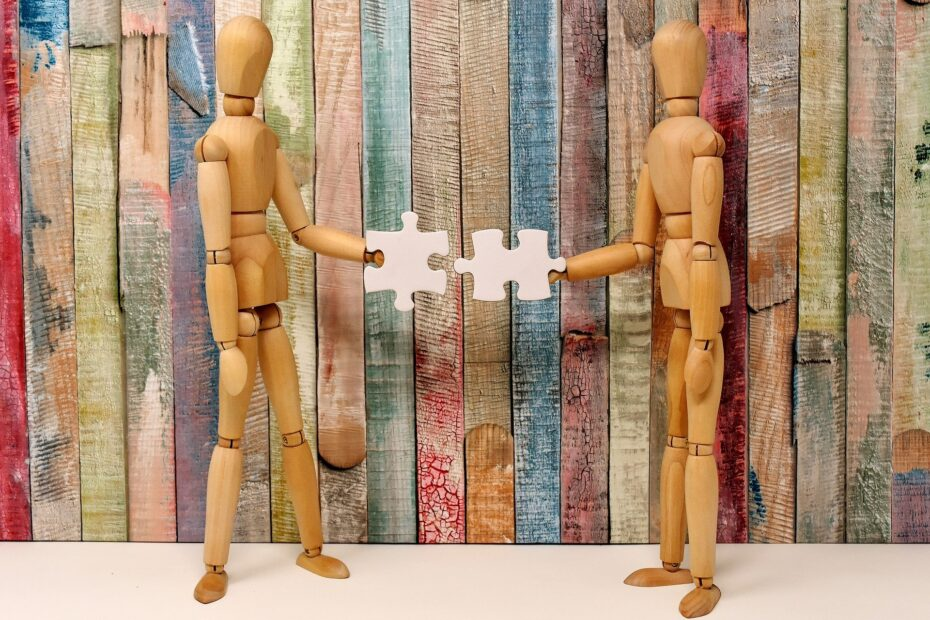 two wooden figures holding jigsaw pieces, aiming to join them together